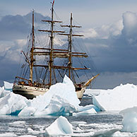 The tallship Europa, a three-masted barque seen through gap in iceberg, Port Charcot, Antarctica