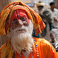 Old Hare Krishna follower dressed in orange dress in front of temple in Govardhan, India