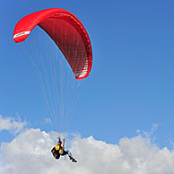 Paraglider in flight with red wing / canopy against blue cloudy sky, Brittany, France