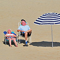 Striped parasol and elderly sunbathers in summer sunbathing on beach along the North Sea coast at Koksijde / Coxyde, Belgium